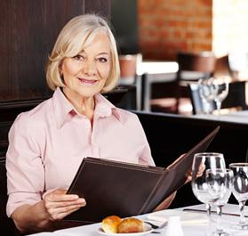 Bild: Frau mit aufgeschlagener Speisekarte am Restauranttisch